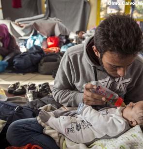 imagen de un padre refugiado dando el biberón a su bebé