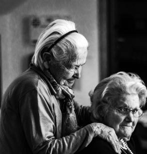 Una mujer apoya sus manos en los hombros de una persona mayor